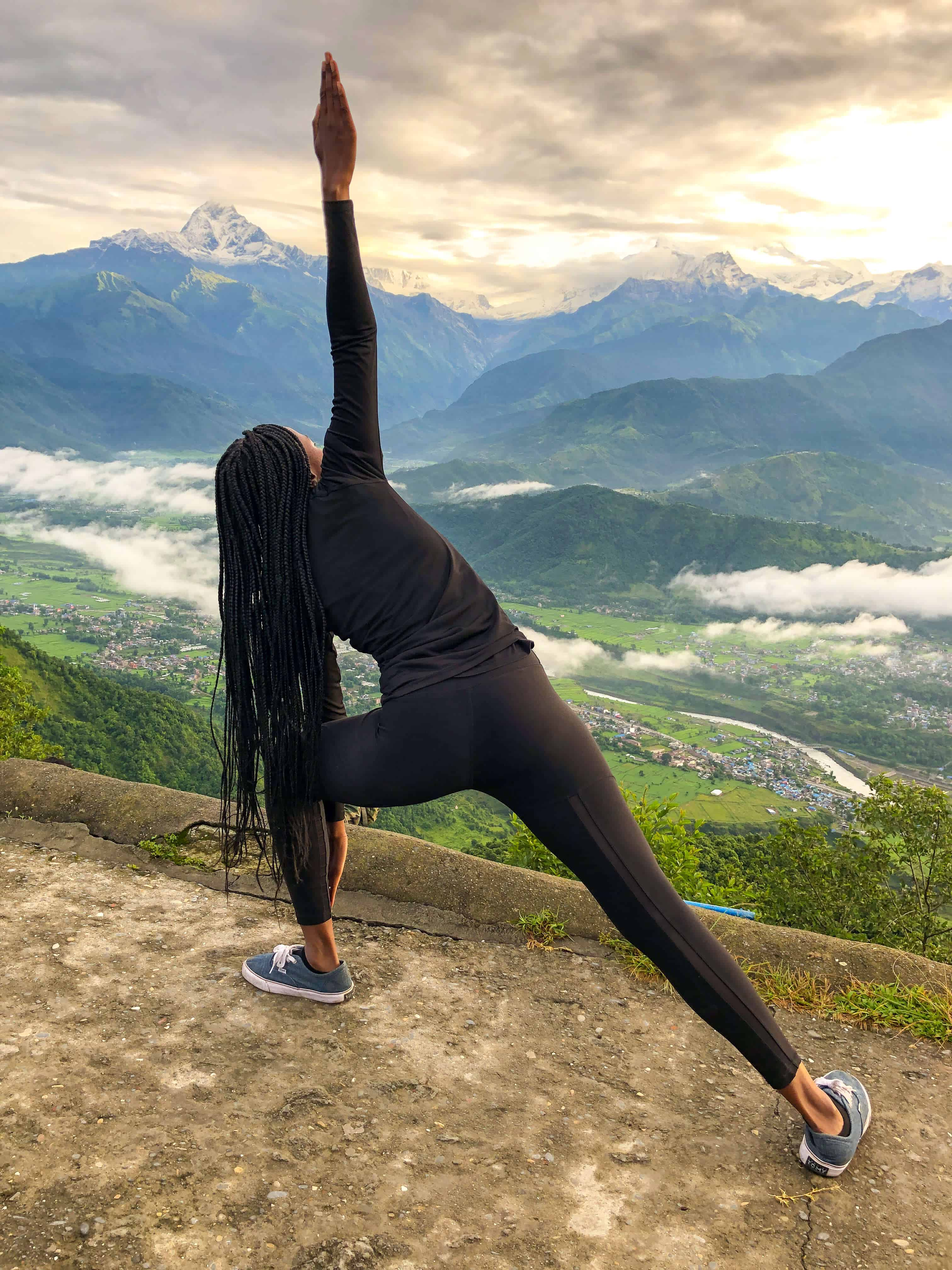Triangle pose, yoga, at sunrise with a view of Annapurna peaks in Sarangkot, Nepal