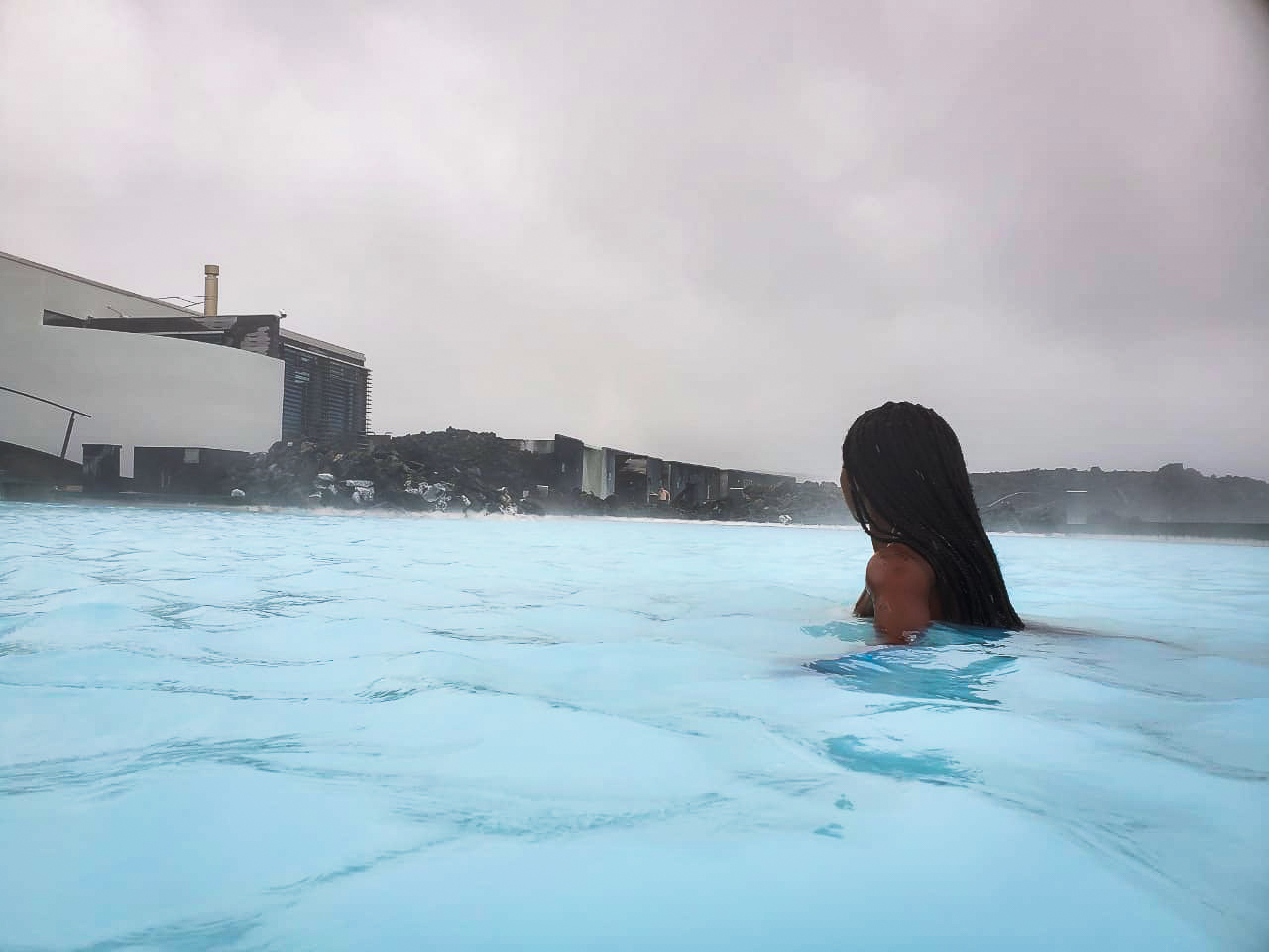 mist over blue grey waters in Iceland's Blue Lagoon with lava fields in the background